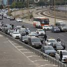 Israelis stand still next to their cars as a siren sounds in memory of victims of the Holocaust, in Tel Aviv, Israel (AP)