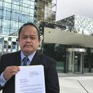 Lawyer Jude Sabio from the Philippines poses for a portrait as he holds a 77-page file outside the International Criminal Court in The Hague (AP)
