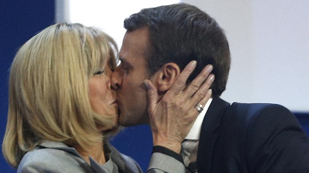 Sealed with a kiss: Emmanuel Macron and his wife Brigitte celebrate in Paris (AP)