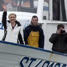 French far-right leader and candidate for the presidential election Marine le Pen waves from a fishing trawler as she arrives from a sea trip in Grau-du-Roi, southern France (AP)