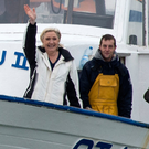 Marine Le Pen waves from a fishing trawler as she arrives from a sea trip in Grau-du-Roi, southern France, yesterday. Photo: Jean-Paul Bonincontro