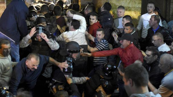 Protesters clash with police to enter the parliament building in Skopje (AP)