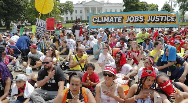 Demonstrators sit on the ground in front of the White House (AP)