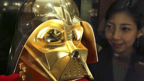 Ginza Tanaka employee Momoko Marutani looks at the gold mask of Darth Vader at the jewellery shop in Tokyo (AP)