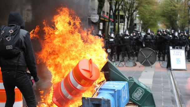 Police try to disperse May Day marchers in Portland, Oregon after some began throwing missiles at officers (The Oregonian/AP)