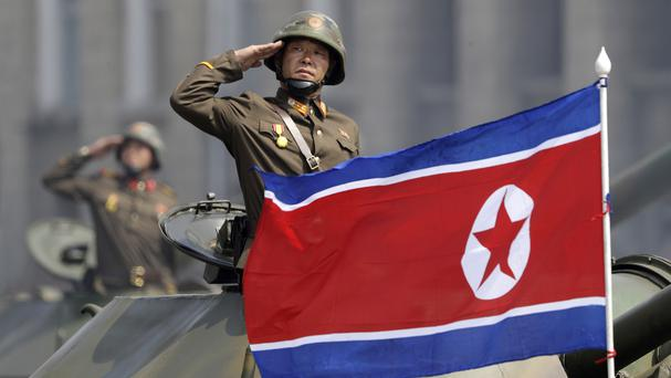 A North Korean national flag flutters as soldiers in tanks salute leader Kim Jong Un during a military parade in Pyongyang (Wong Maye-E/AP)