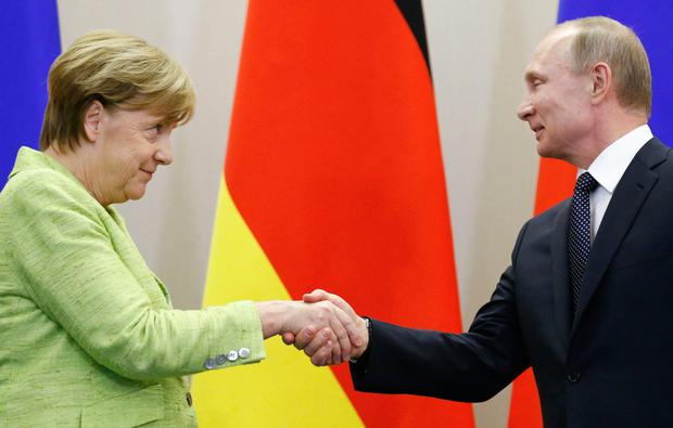 Russian President Vladimir Putin and German Chancellor Angela Merkel shake hands during a joint news conference yesterday. Photo: Reuters