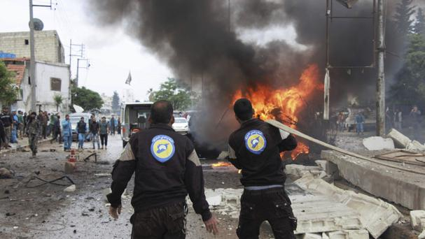 Syrian White Helmet civil defence workers extinguishing a burning car at the explosion scene, in Azaz town. (Azaz Media Office/AP)