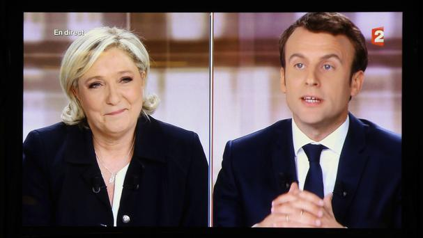 A television screen shows the live debate with Marine Le Pen and Emmanuel Macron (Bob Edme/AP)