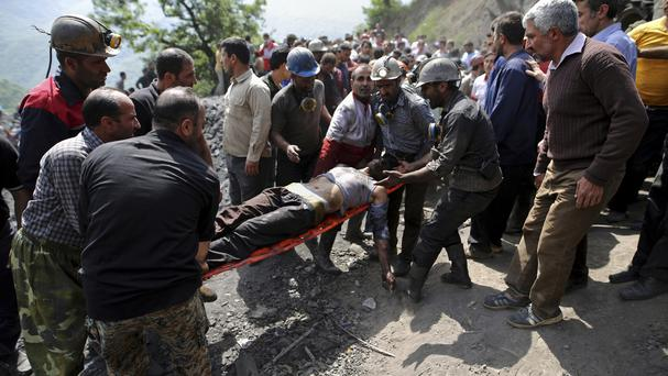 Rescue personnel carry an injured worker after a coal mine explosion, near Azadshahr in northern Iran. (AP/Tasnim News Agency, Mostafa Hassanzadeh)