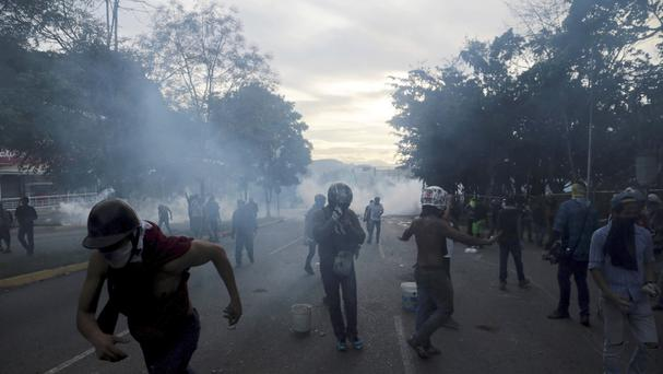 Demonstrators take cover during clashes at El Hatillo municipality outside Caracas, Venezuela. (AP/Fernando Llano)