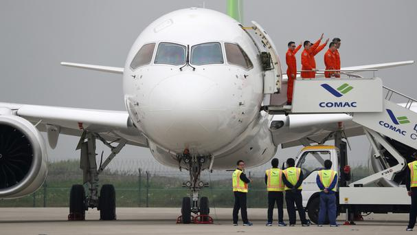 Crew wave as they exit a C919 passenger jet after its first flight at Pudong International Airport in Shanghai, China (AP/Andy Wong)