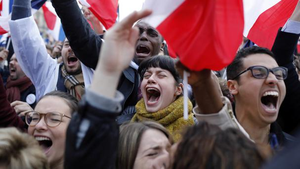 Supporters of Emmanuel Macron celebrate after exit polls project he will be named the next French president (Laurent Cipriani/AP)