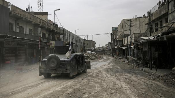 A humvee of the Iraqi federal police drives through an abandoned street in western Mosul (Bram Janssen/AP/PA)