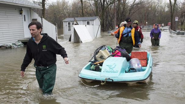 Residents use a paddleboat as they bring supplies through flooded streets of the Ile-Mercier district of Ile-Bizard, Quebec (Ryan Remiorz/The Canadian Press via AP)