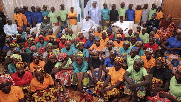 President Muhammadu Buhari, centre rear, with the Chibok schoolgirls before leaving for London (Nigeria State House/AP)