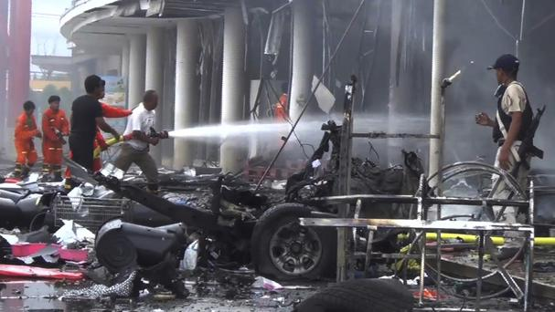 Firefighters try to extinguish a fire after a bomb hidden in a car exploded outside a large shopping centre in Pattani province, southern Thailand (AP)