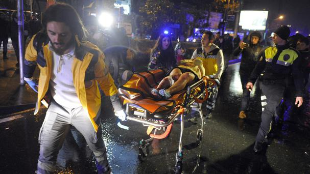 Medics carry a wounded person at the scene after an attack at a popular nightclub in Istanbul (IHA via AP)