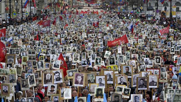 Russians carry portraits of their ancestors who participated in the Second World War as they celebrate Victory Day in St Petersburg (AP)