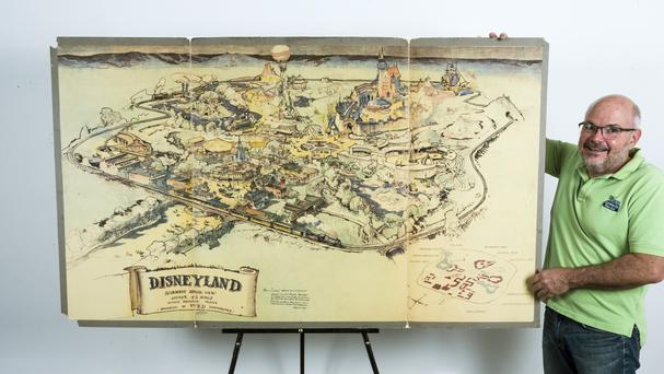 Mike Van Eaton stands next to a hand-drawn map from 1953 that shows Walt Disney's original ideas for Disneyland (AP/Damian Dovarganes)
