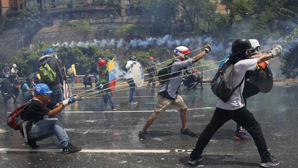 Anti-government protesters aim a giant slingshot at security forces in Caracas (AP)