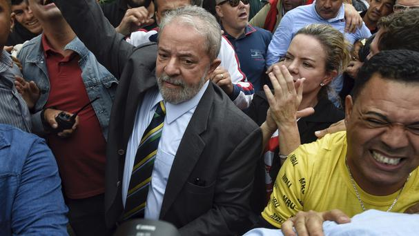 Former president Luiz Inacio Lula da Silva is greeted by supporters at the Federal Justice building in Curitiba (AP)
