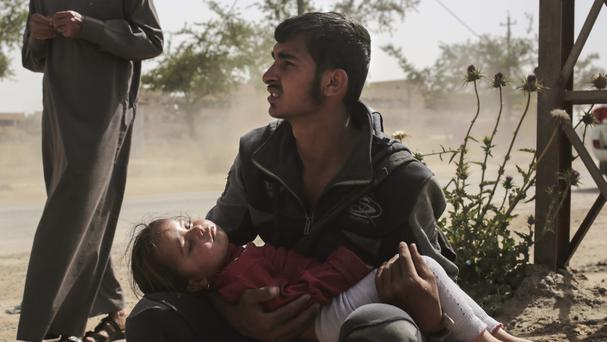 A girl sleeps in her father's arms in western Mosul after fleeing from fighting between Iraqi forces and the Islamic State group (Bram Janssen/AP)