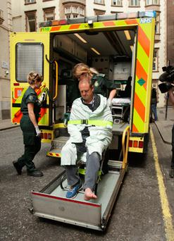 BBC cameraman Giles Wooltorton is loaded into an ambulance after the car carrying Jeremy Corbyn ran over his foot as it arrived at the Institute of Engineering in London yesterday. Photo: PA