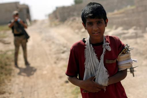 A displaced Iraqi boy flees from a frontline as members of Iraqi Rapid response forces clash with Islamic State fighters, in north west of Mosul, Iraq, May 9, 2017. REUTERS/Danish Siddiqui