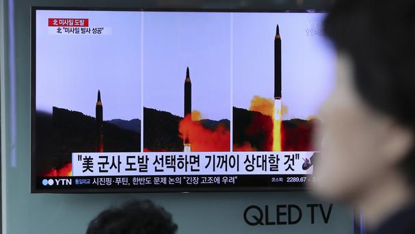 People at Seoul railway station watch a TV news programme showing images of North Korea's missile launch (AP Photo/Lee Jin-man)