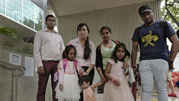 The asylum seekers pose outside the building of Hong Kong's immigration department. (AP/Vincent Yu)