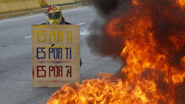 A demonstrator holds a sign that doubles as a shield that reads in Spanish