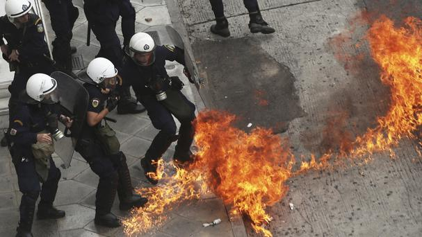 Riot police officers try to avoid a petrol bomb thrown by protester during a general strike demonstration in Athens. (AP/Petros Giannakouris)