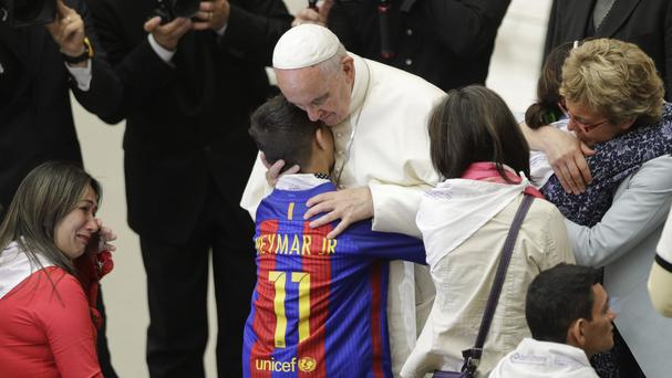 Pope Francis hugs a boy during an audience with Huntington's disease families at the Vatican (AP)