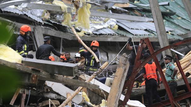 Sri Lankan rescuers search for trapped people in the debris after a building collapsed (AP)