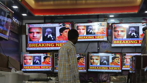 An Indian boy watches as television channels show news about the case of Indian naval officer Kulbhushan Jadhav (AP)