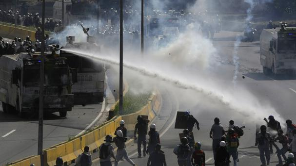 A water cannon sprays at protesters trying to reach the Interior Ministry in Caracas (Fernando Llano/AP)