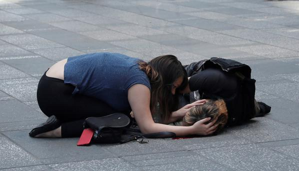 An injured pedestrian is tended by a passer-by