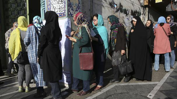 Iranian voters enter a polling station for the presidential elections in Tehran (AP)