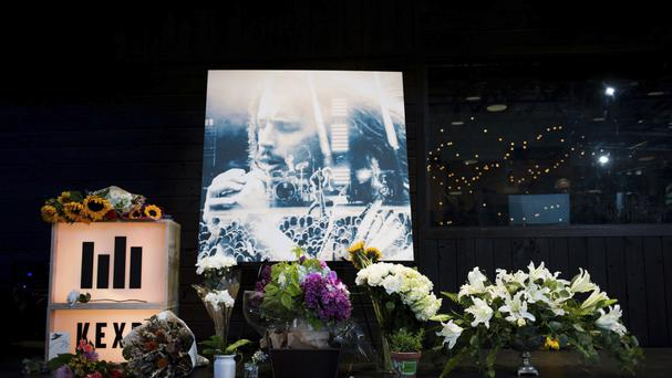 Flowers and cards sit in front of a large image with a depiction of Chris Cornell on it during a memorial in Seattle (AP)