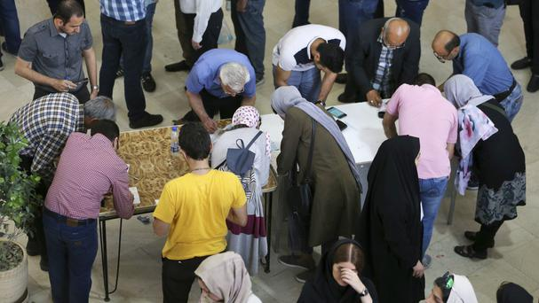 Voters fill in their ballots while voting for the presidential election at a polling station in Tehran, Iran (AP)