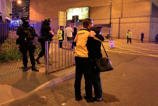 Shocked concert-goers console one another after the blast. Photo: PA