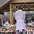 A Sharia law official canes a man convicted of adultery in Banda Aceh, Indonesia (AP)