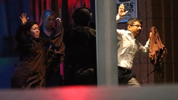 Hostages run to freedom from the cafe during the siege in December 2014 (AP Photo/Rob Griffith, File)