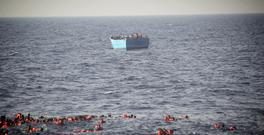 Migrants wearing life vests are seen floating in the water before being rescued at sea (MOAS via AP)