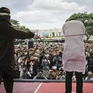 An official whips one of two men convicted of gay sex in Indonesia. (AP/Heri Juanda)