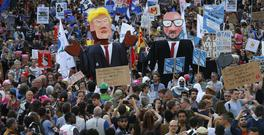 Protesters carry effigies of US President Donald Trump and Belgian PM Charles Michel during a demonstration in the centre of Brussels (AP)