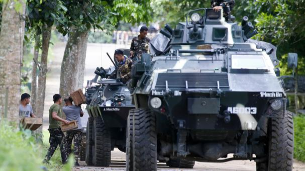 Troops load ammunition and supplies as a convoy heads to Marawi city (AP)