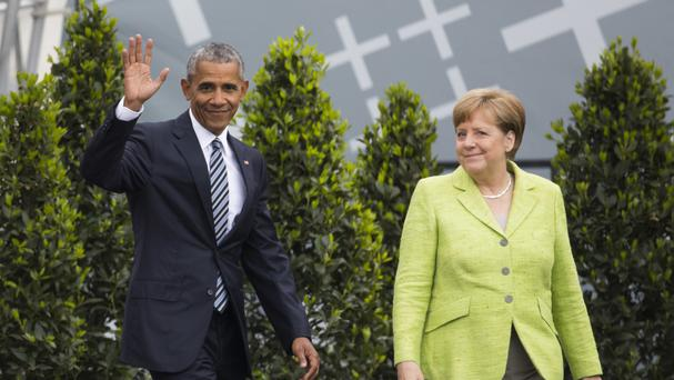Barack Obama waves to the crowd next to German chancellor Angela Merkel (AP)