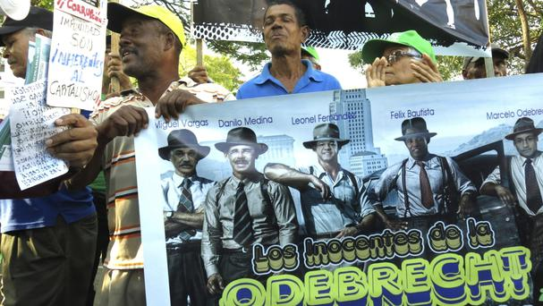 Demonstrators carry a banner amid a corruption probe (Ezequiel Abiu Lopez/AP)